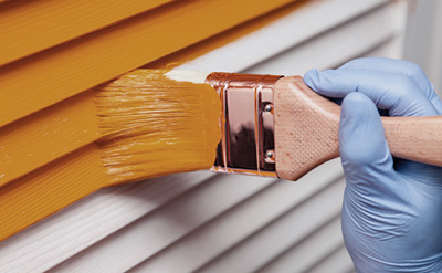 Image of a person paining a wall orange