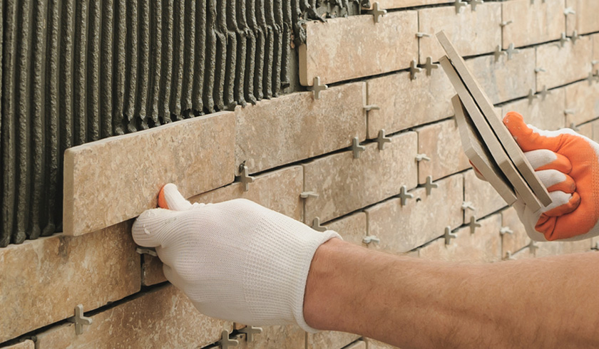 Image of a man tiling a wall